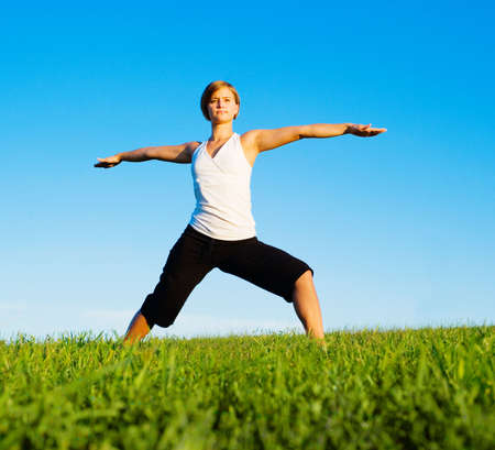 Young woman doing yoga in a sunny meadow, from a complete series of photos. Stock Photo - 5640675