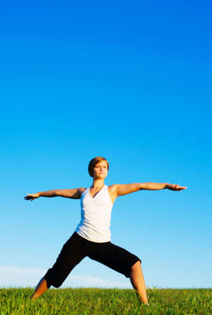 Young woman doing yoga in a sunny meadow, from a complete series of photos. Stock Photo - 5640647