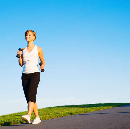 Young woman walking with weights, from a complete series of photos. Stock Photo