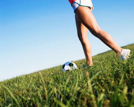 Young woman playing soccer in a field, from a complete series of photos. Stock Photo