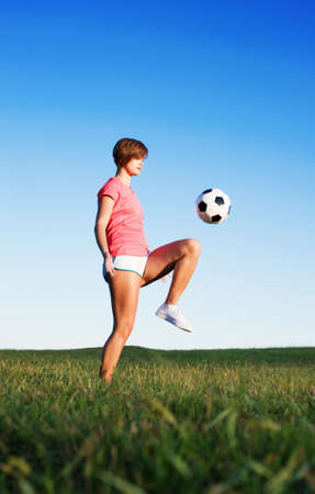 Young woman playing soccer in a field, from a complete series of photos. photo
