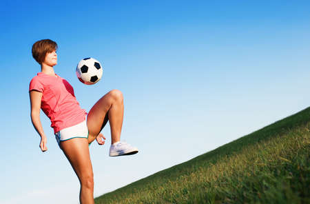 Young woman playing soccer in a field, from a complete series of photos. Imagens