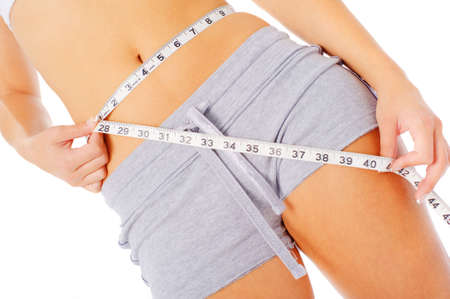 slim tummy: Young woman measuring herself with a measuring tape, from a complete series of photos.