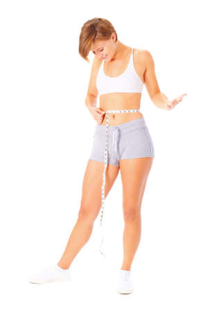 Young woman measuring herself with a measuring tape, from a complete series of photos.