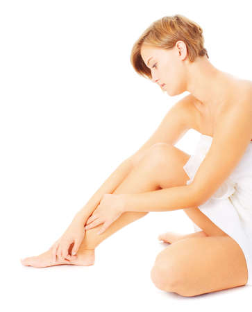 Woman in towel massaging her leg, from a complete series of photos. photo