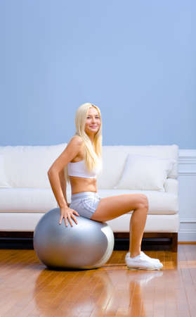 Young woman sits on an exercise ball in the living room. She is dressed in sportswear. Vertical shot.