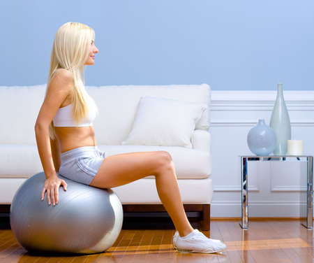 exercise room: Side view of young woman sitting on exercise ball in living room.  Horizontal shot.
