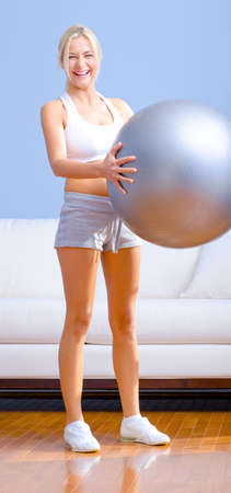 Young woman wearing sportswear holds a balance ball in a living room.  Vertical shot. Stock Photo - 6248763