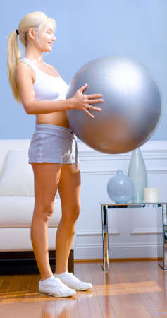 Side view of young woman holding an exercise ball in the living room. A sofa and side table are in the background.  Vertical shot. Stock Photo