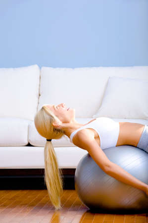 Side view of young woman wearing sportswear and lying on a balance ball in a living room.  Vertical shot. photo