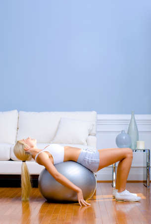 Side view of young woman wearing sportswear and lying on a balance ball in a living room.  Vertical shot.