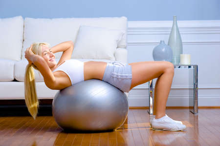 working out: Side view of young woman wearing sportswear and doing crunches on a balance ball in living room.  Horizontal shot.