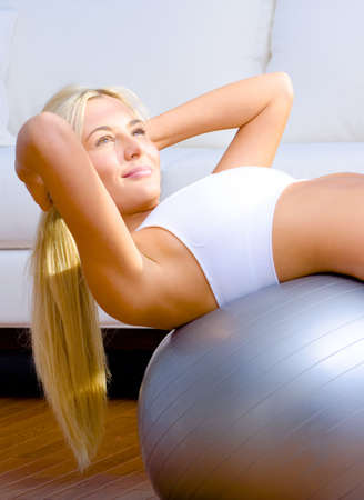 Young woman does crunches on a balance ball in the living room.  Vertical shot. photo