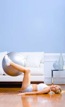 Side view of a young woman in sportswear using an exercise ball in the living room.  Vertical shot. photo