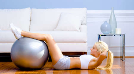 crunches: Side view of young woman in sportswear doing crunches in a living room.  Horizontal shot.
