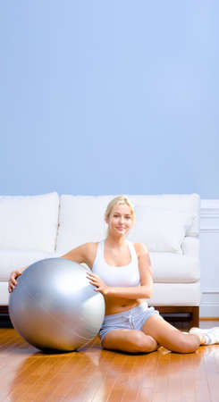 Young woman in sportswear sits next to an exercise ball in her living room.  Vertical shot. Stock Photo - 6248971