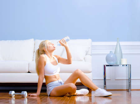 Side view of a young woman drinking bottled water after exercising.  Horizontal shot. photo