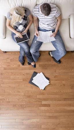 ハイアングルビュー: ノート パソコンと書類とソファの上に座っている若いカップルの高角度のビュー。垂直方向のショット。