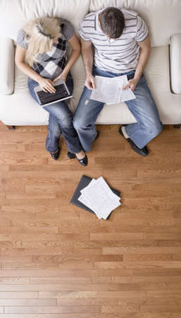 High angle view of young couple sitting on a couch with a laptop and paperwork. Vertical shot.