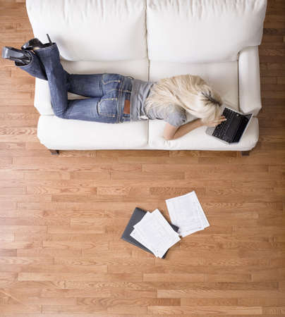 lying on couch: High angle view of a woman using her laptop with papers scattered about. Vertical shot. Stock Photo