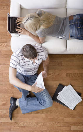 High angle view of a young couple with a laptop and paperwork. Vertical shot. Stock Photo - 6249362