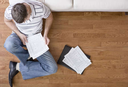Young man sits on the floor as he looks through paperwork. Horizontal shot. Stock Photo - 6249360