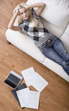 High angle view of a young woman frustrated while doing paperwork. Vertical shot. Stock Photo - 6249357