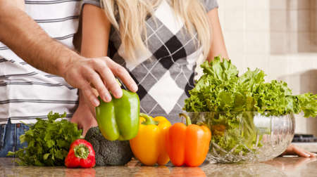 Cropped view of a young couple preparing vegetables on their kitchen counter. Horizontal shot. Stock Photo - 6249361