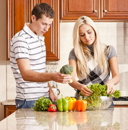 Young couple in kitchen make salad with fresh vegetables. Square shot. photo