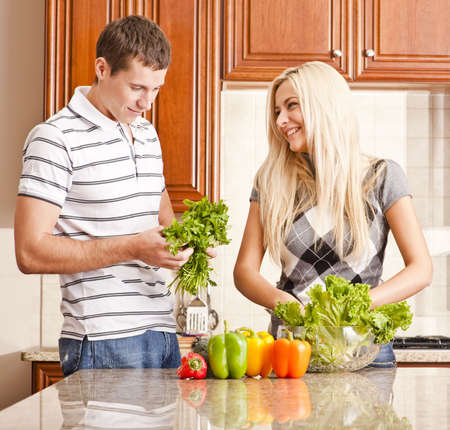 Young couple in the kitchen enjoy making a salad with fresh vegetables. Square shot. photo