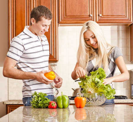 Young couple in the kitchen enjoy preparing salad with fresh vegetables. Square shot. photo