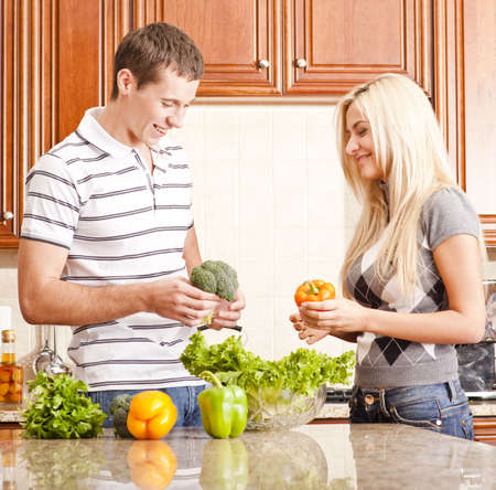 Young couple in the kitchen have fun while making a fresh salad. Square shot. Stock Photo - 6249264