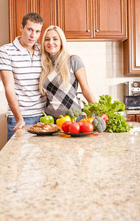 Young couple smile into the camera behind a kitchen counter.  The counter is displaying a variety of fresh vegetables. Vertical shot. photo