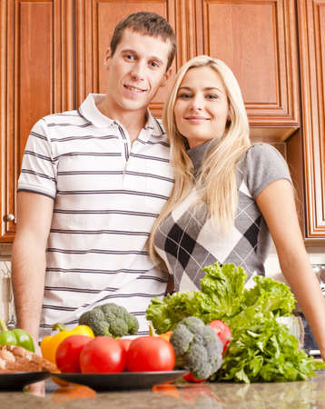 Low angle view of young couple smiling into the camera from behind a kitchen counter. The counter is holding a selection of fresh vegetables. Vertical shot. photo