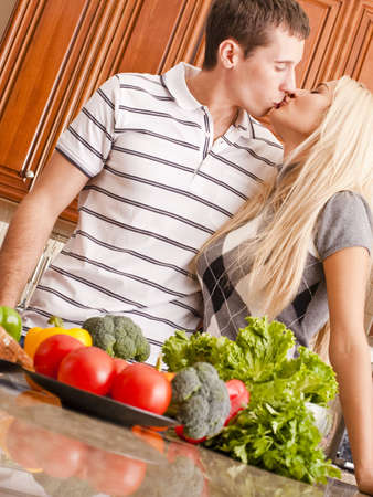 tilted view: Low angle, tilted view of young couple kissing behind a kitchen counter holding fresh vegetables. Vertical shot.
