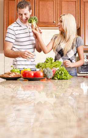 Young couple in a kitchen joke around with fresh vegetables. Vertical shot Stock Photo - 6249096