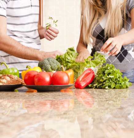 Young couple pick through fresh vegetables behind a kitchen counter. Square shot. photo