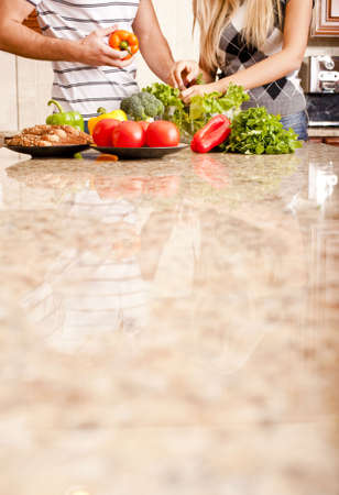 Young couple picks through fresh vegetables at the far end of a kitchen counter. Vertical shot. photo