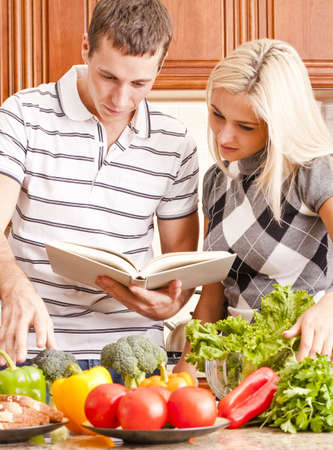 Young couple follows a recipe book. The kitchen counter is full of fresh vegetables. Vertical shot.