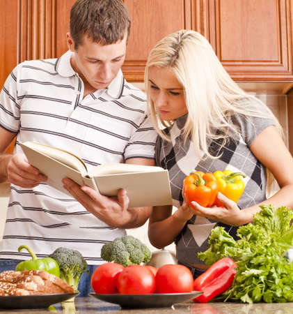 Young couple look at a recipe book in the kitchen. The counter is full of fresh vegetables. Square shot. Stock Photo
