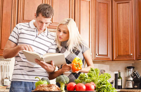Young couple in the kitchen read an open recipe book. The counter is full of fresh vegetables. Horizontal shot.
