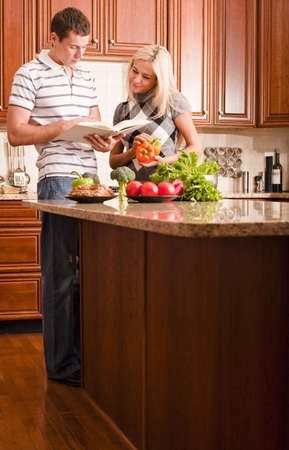 Young couple read through a recipe book in the kitchen with a counter full of fresh vegetables. Vertical shot. photo