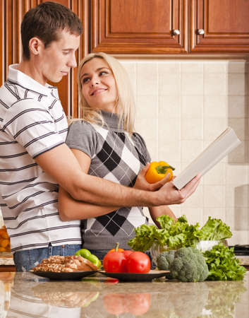 Young woman looks back affectionately at a young man as he reads a recipe book. A kitchen counter holds a variety of fresh vegetables in the foreground. Vertical shot. photo