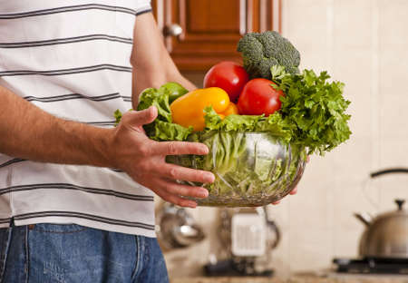 Man in striped shirt holding a bowl of vegetables in kitchen. Horizontal shot. Stock Photo - 6249272