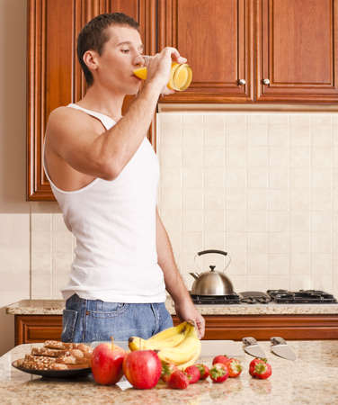 Young man wearing tank top and jeans in kitchen drinking a glass of orange juice. Vertical shot. photo