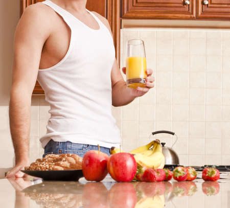 Young man wearing tank top and jeans in kitchen holding a glass of orange juice. Horizontal shot.