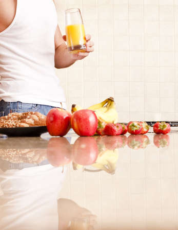 Young man wearing tank top and jeans in kitchen holding a glass of orange juice. Vertical shot. Stock Photo - 6248638