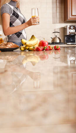 Young woman in kitchen holding a glass of orange juice. Vertical shot. Stock Photo - 6248460