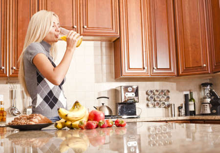 Young woman in kitchen drinking a glass of orange juice. Horizontal shot. photo