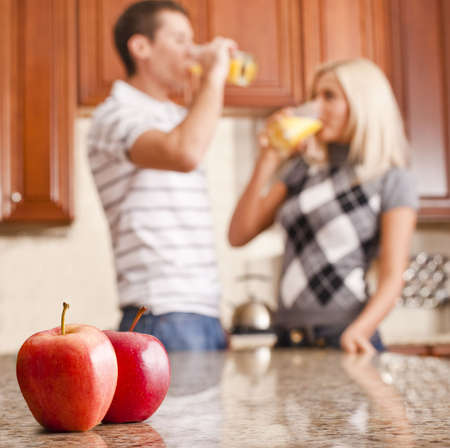 Young couple in kitchen drinking a glass of orange juice, two apples on counter in foreground. Square format. Stock Photo - 6249290